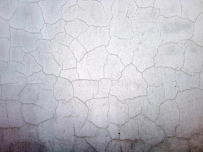 Texture of a white cracked wall. White old shabby wall stock image