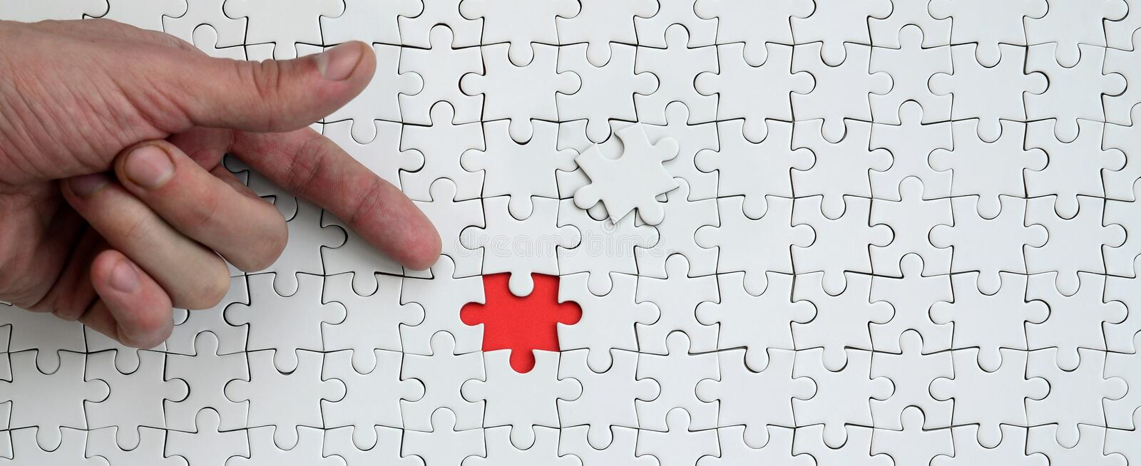 The texture of a white jigsaw puzzle in the assembled state with one missing element, forming a red space, pointed to by the finge. R of the male hand royalty free stock photo