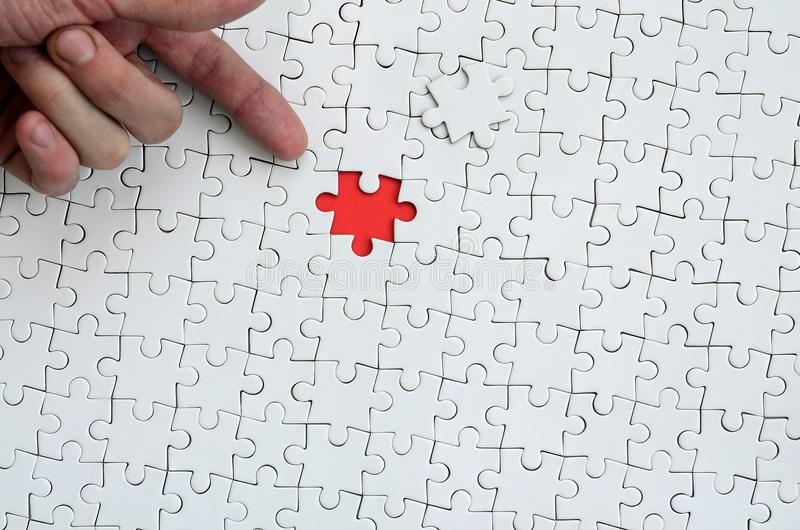 The texture of a white jigsaw puzzle in the assembled state with one missing element, forming a red space, pointed to by the finge. R of the male hand royalty free stock images