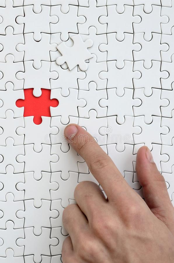 The texture of a white jigsaw puzzle in the assembled state with one missing element, forming a red space, pointed to by the finge. R of the male hand stock photo