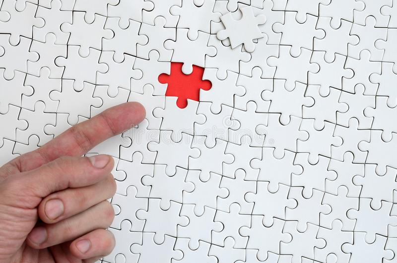 The texture of a white jigsaw puzzle in the assembled state with one missing element, forming a red space, pointed to by the finge. R of the male hand stock images
