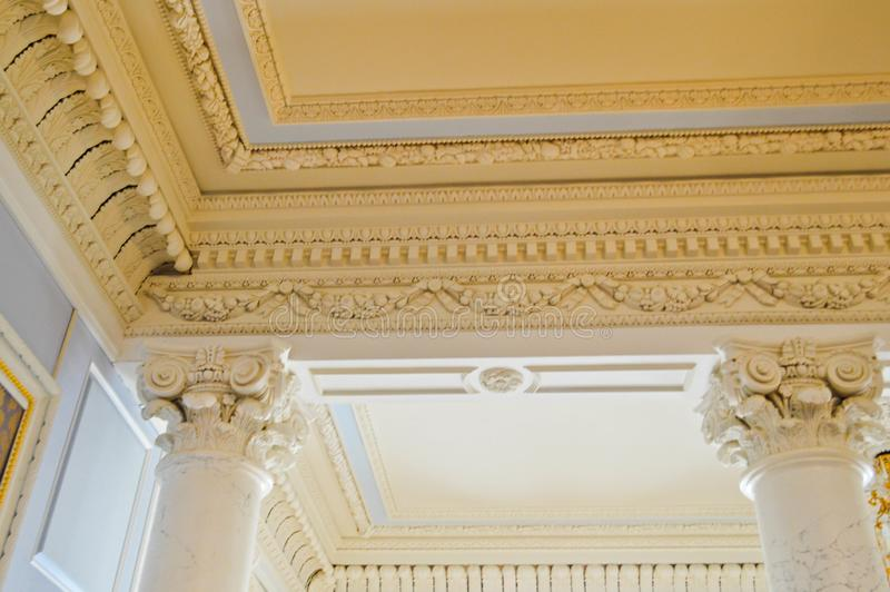 The texture of the white stone ceiling with patterns and beautiful plaster moldings and antique columns. The background royalty free stock photography