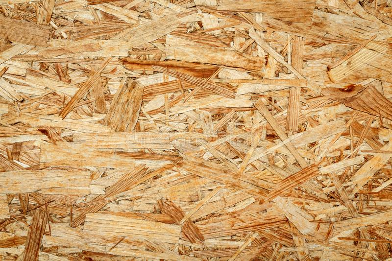 - Texture of wooden chipboard. The texture of the wooden surface of pressed chips and sawdust closeup royalty free stock image