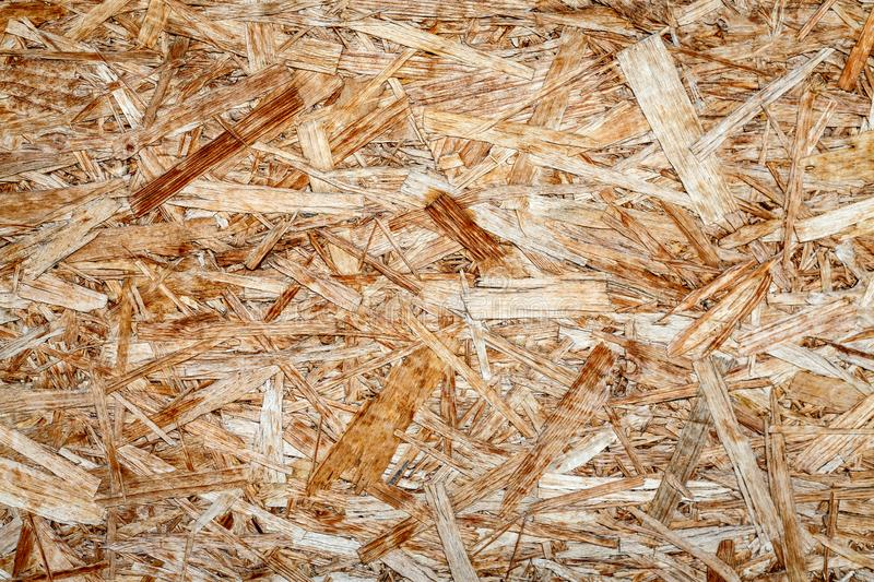 Texture of wooden chipboard. The texture of the wooden surface of pressed chips and sawdust closeup stock images