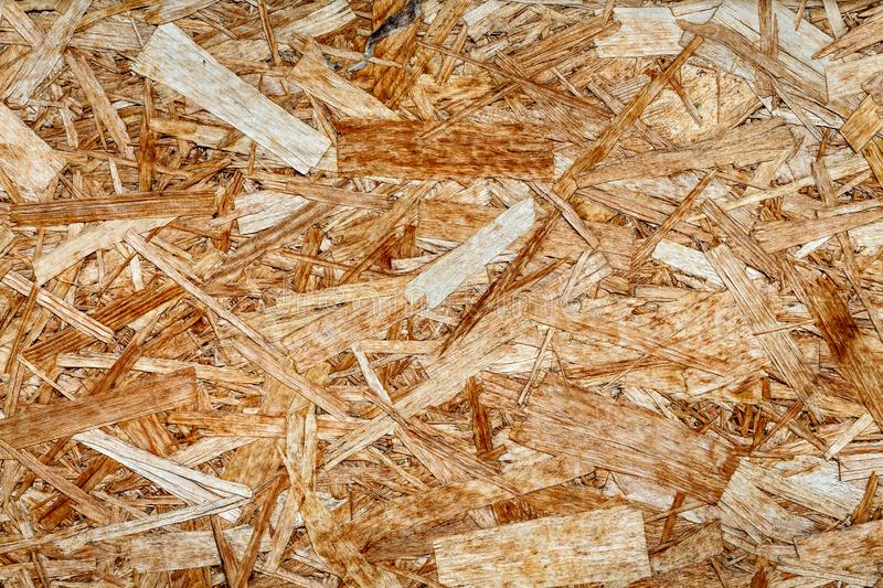 Texture of wooden chipboard. The texture of the wooden surface of pressed chips and sawdust closeup stock photography