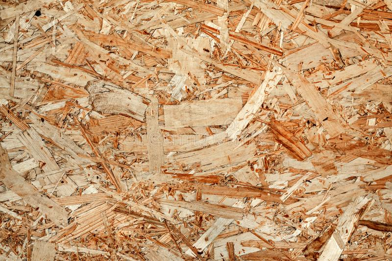 Texture of wooden chipboard. The texture of the wooden surface of pressed chips and sawdust closeup stock image