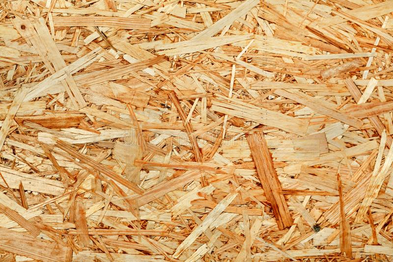 Texture of wooden chipboard. The texture of the wooden surface of pressed chips and sawdust closeup royalty free stock photos