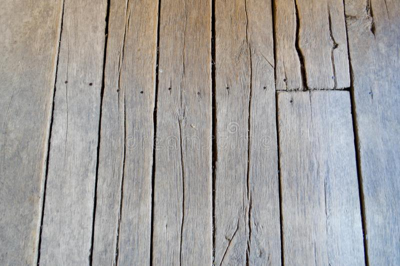 Texture of wooden unpainted old boards with seams, cracks and nail caps. The background stock photography