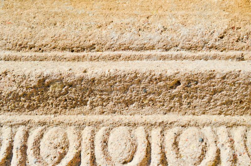 The texture of the yellow sand stone of old stone with patterns and stripes. The background royalty free stock photography