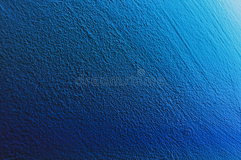 Textured aqua blue painted wall background and texture. The wall is illuminated with cyan light. Grain shows stock photo