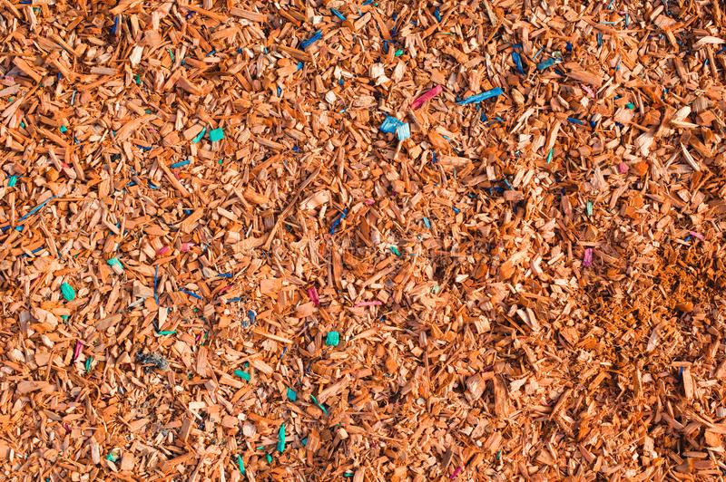 Textured background decorative colored sawdust for finishing flowerbeds in the winter season. Yellow orange sawdust royalty free stock photography