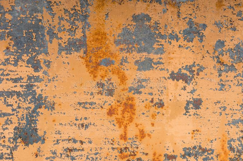 Textured background of a faded yellow paint with rusted cracks on rusted metal. Grunge texture of an old cracked metal stock photo