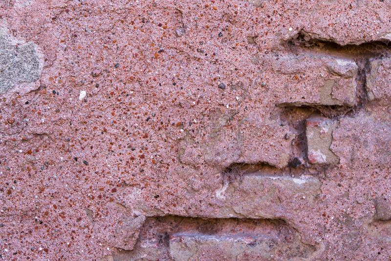 Texture cement and bricks of the ancient wall in pink and red tones royalty free stock photography
