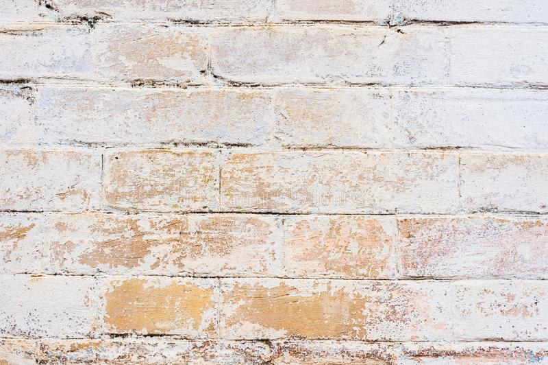 Textured background of old yellow brickwork covered with cracked and partially falling off whitewash. Nice brick stock photo