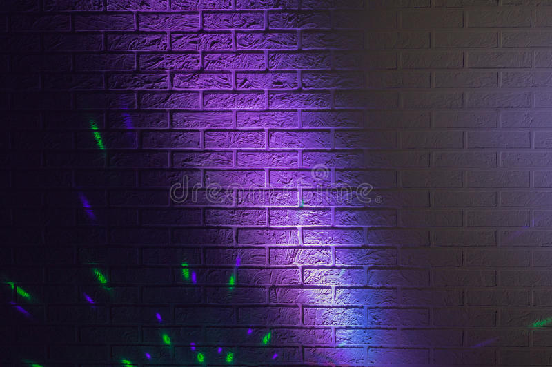 Textured brick wall lit by colored lights. Textured brick wall lit by many colored lights stock images