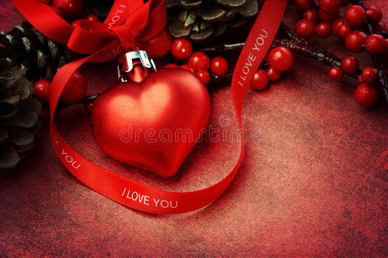 Textured Christmas background with heart ornament. Textured christmas background with heart shaped ornament and red 'I love you' ribbon royalty free stock image
