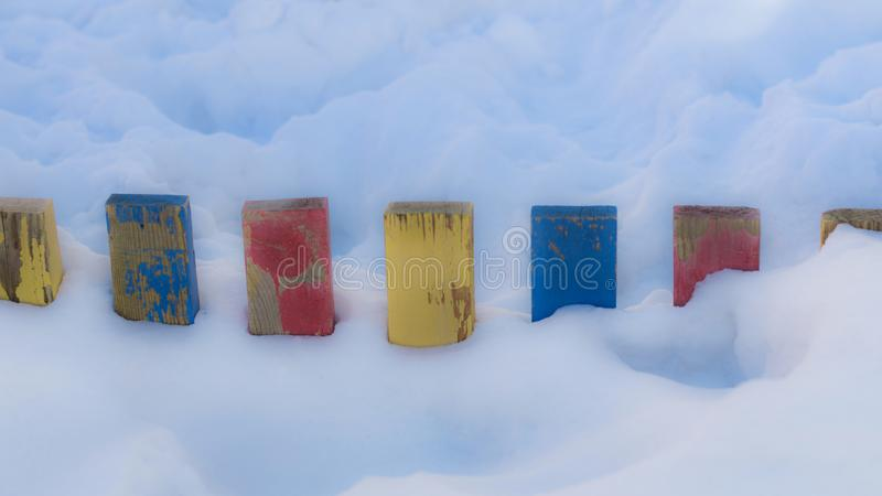 Textured Colorful Painted Blue, Red, Yellow Wooden Picket Fence Planks In Deep Snow, Colorful Rustic Style Background For Vintage royalty free stock photos