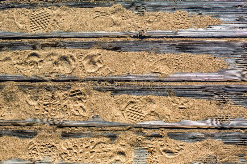 Textured detailed wooden flooring from planks on the sand on the beach with footprints of shoes. Fragment. Texture. In the Algarve, Portugal stock photography