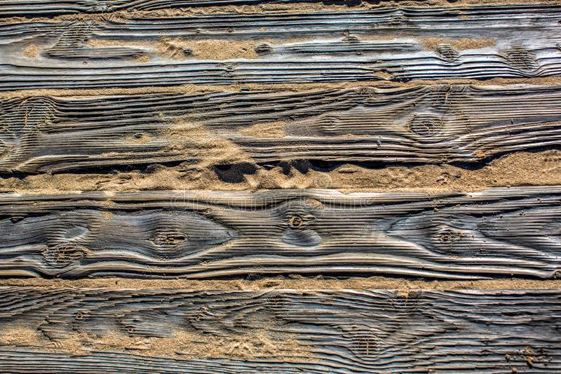 Textured detailed wooden flooring from planks on the sand on the beach with footprints of shoes. Fragment. Texture. In the Algarve, Portugal royalty free stock image