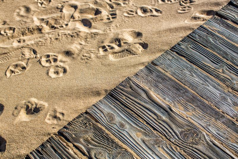 Textured detailed wooden flooring from planks on the sand on the beach with footprints of shoes. Fragment. Texture. In the Algarve. Portugal royalty free stock photo