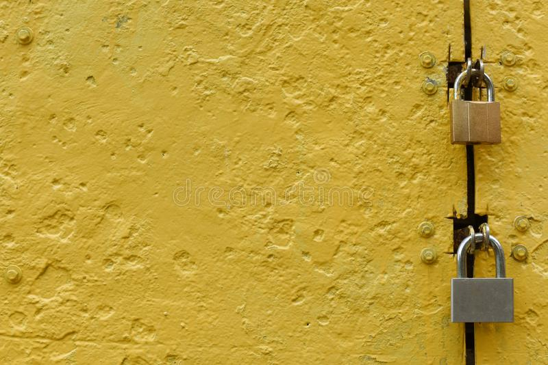 Textured metal door painted with yellow paint with two metal locks. stock photography