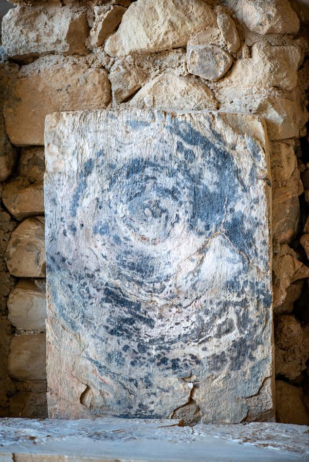 Textured sand stone with an circular pattern. In front of an ancient stone wall stock photography