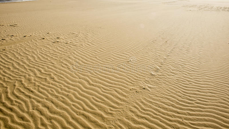 Textured sea sand. A high view of textured sea sand stock image