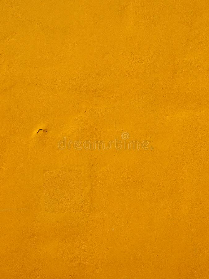 Textured wall surface painted a rich bright yellow colour with surface cracks. A textured wall surface painted a rich bright yellow colour with surface cracks stock photo