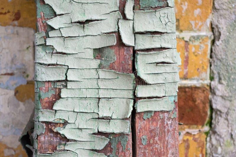 Texturen av det gamla spruckna trät som målas i blått på en bakgrund av en gammal tegelstenvägg royaltyfria foton