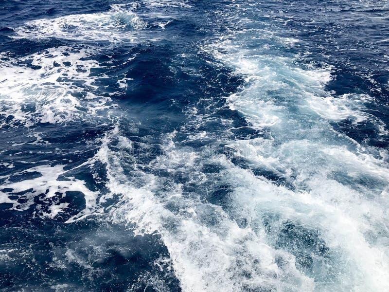 Texturen av det sjuda salta vattnet för det blåa havet med vågor, spill, bubblor, skum, spår, brister efter en snabb sväva vagn,  fotografering för bildbyråer
