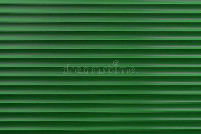 Texturen av en metallrulle av olika färger Bakgrunden av järnrullgardinerna Skyddande rullslutare för ingångsdörr royaltyfria bilder