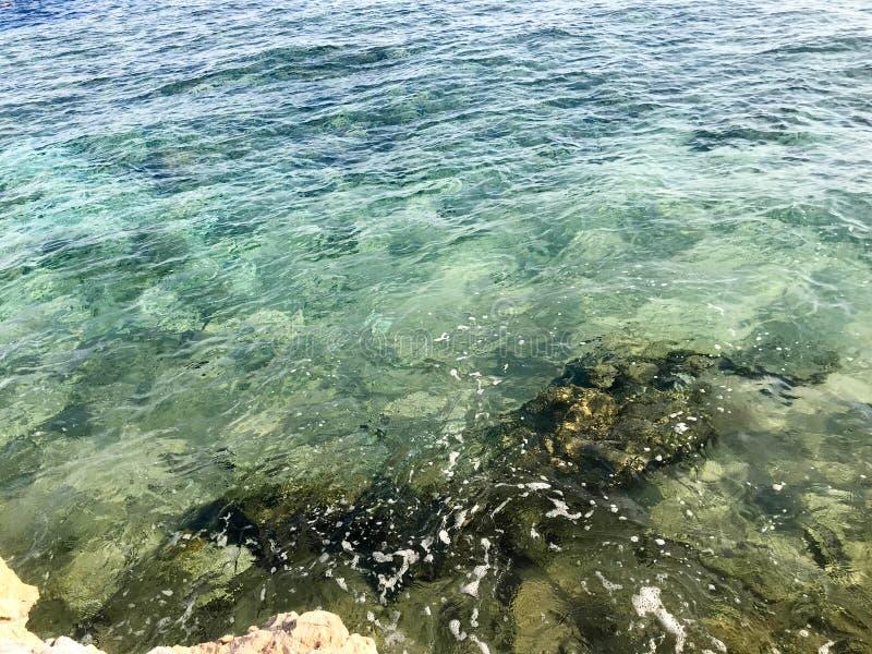 Texturen av en sandig strand för härlig sten, ett land, en strand och ett grönaktigt blått vatten, havet på en tropisk varm varm  royaltyfri fotografi