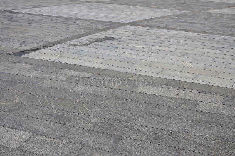 Texturen av granitstenläggningtegelplattor från en variation av fyrkanten formade plattformar under ljus sunligh royaltyfri fotografi
