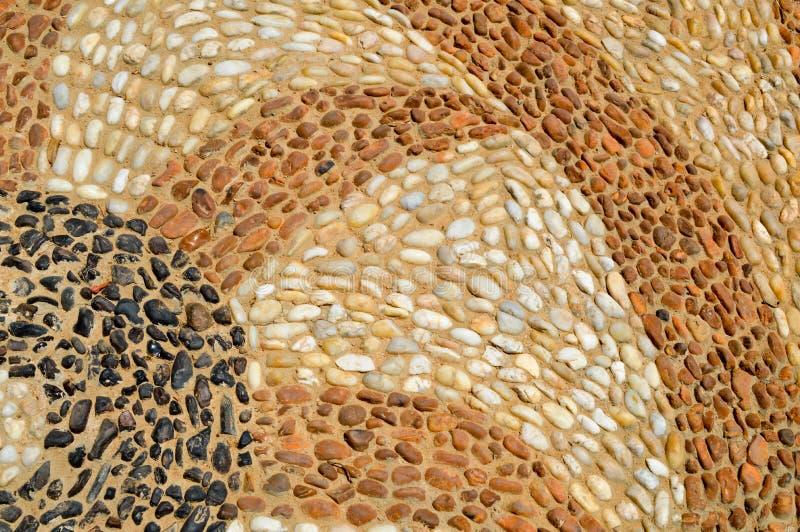 Texturen av stenväggen, vägen från liten runda och ovalstenar med gjorde sammandrag linjer av hjärta mönstrar sandigt arkivbilder