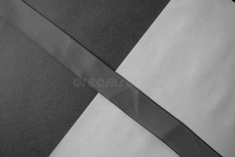 Texturen av svartvitt papper är härlig med ett band som göras av delikat trendigt glamoröst tyg grönska för abstraktionbakgrundsg royaltyfria foton