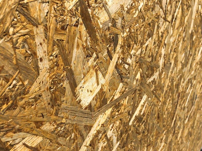 Texturen vanuit een invalshoek van houten geel bouwmateriaal van spaanders en samengeperst zaagsel OSB, het afval van de meubilai royalty-vrije stock foto's