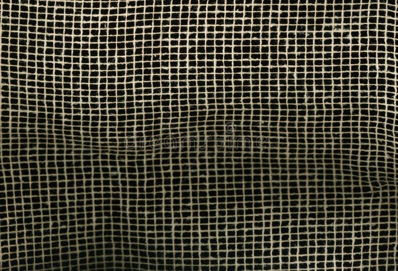 Textureof-Gewebe Leinwand-Segeltuch-natürliche Brown-Masche auf schwarzem Hintergrund Makrobeschaffenheitsmusterhintergrund lizenzfreie stockfotografie