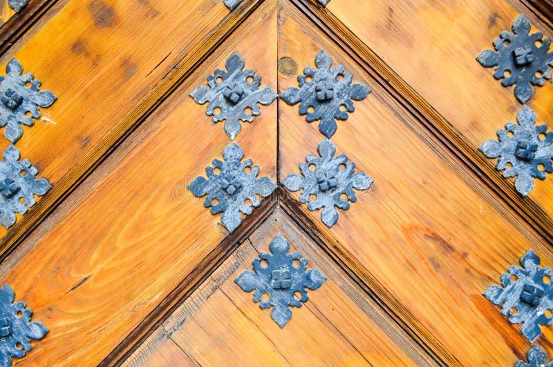 Texturera av robust tränaturlig tjock dörr för gammal forntida medeltida antikvitet med nitar och spikar modeller och lås arkivfoto