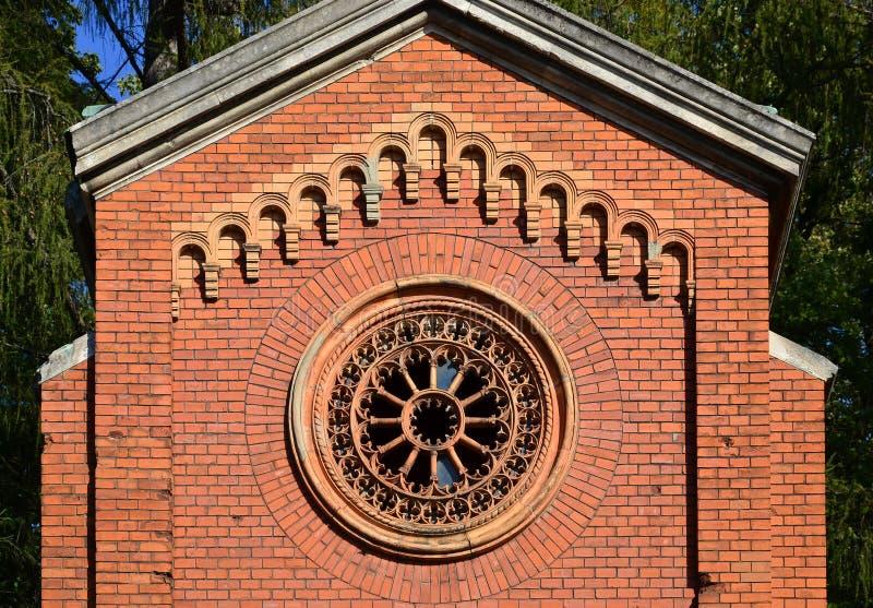 Texturera den främre delen av en forntida tegelstenkrypta med rundan mönstrat snidit fönster i cemeteren royaltyfri foto