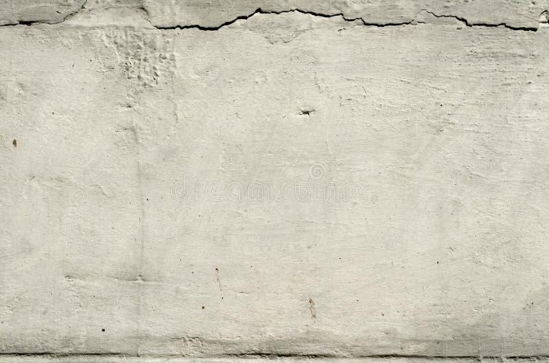 Texturera den gamla betongväggen med rest av murbruk med sprickor royaltyfria bilder