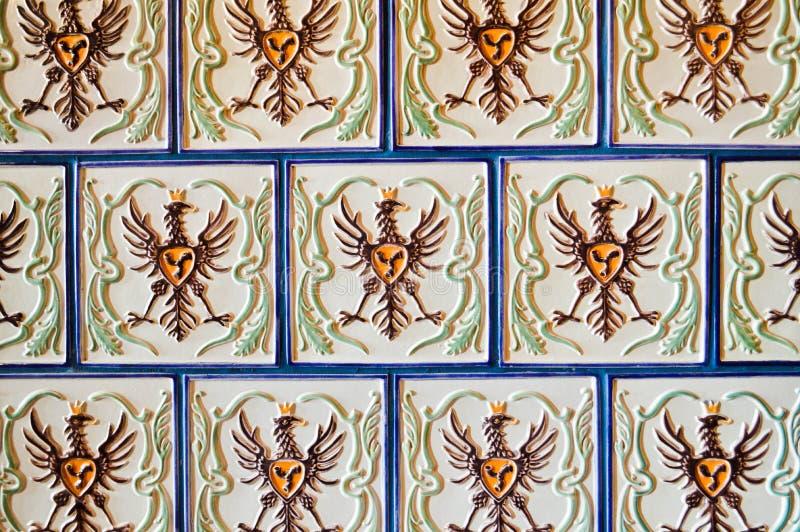 Texturera en härlig fyrkantig vit keramisk tegelplatta med modeller i form av en fågel, örnen, tupp med blåa sömmar grönska för a arkivbild