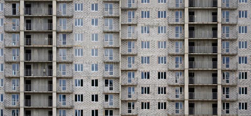 Texturerad modell av vägg för byggnad för hus för rysswhitestone en bostads- med många fönster och balkongen under constructio royaltyfri foto