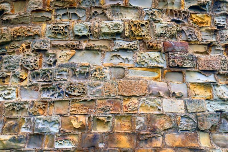 Texturerad stenhuggeriarbetevägg med varierande färger arkivbilder