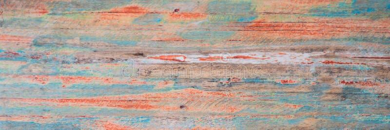 Texturerad träbakgrund - grungy riden ut träyttersida som täckas med gamla blått, och röd skalning målar BANRET, långt format royaltyfria foton