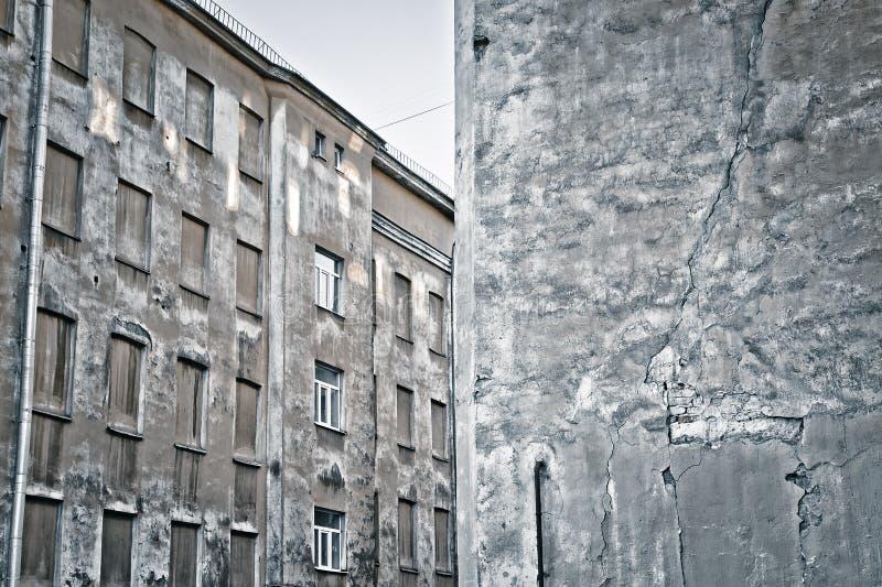 Texturerad vägg och ett hus med blinda fönster arkivfoto
