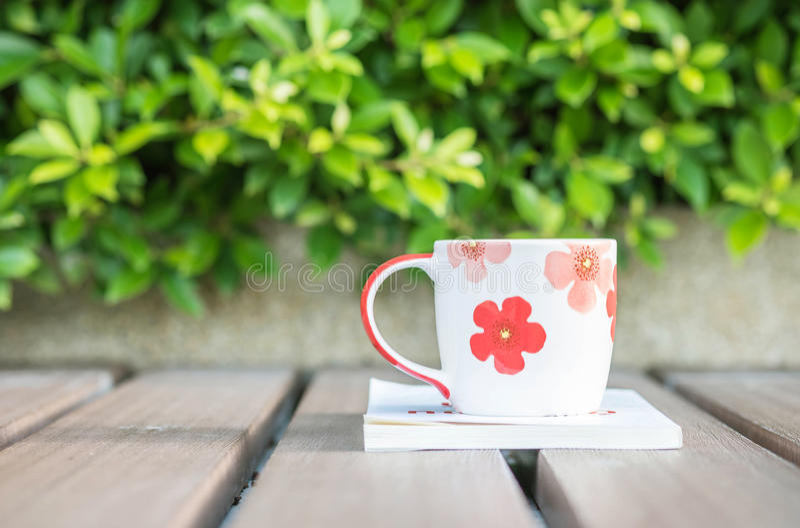 Texturerade den härliga koppen kaffe för closeupen på den vita boken på den suddiga trätabellen och den gröna växten i trädgården arkivfoto