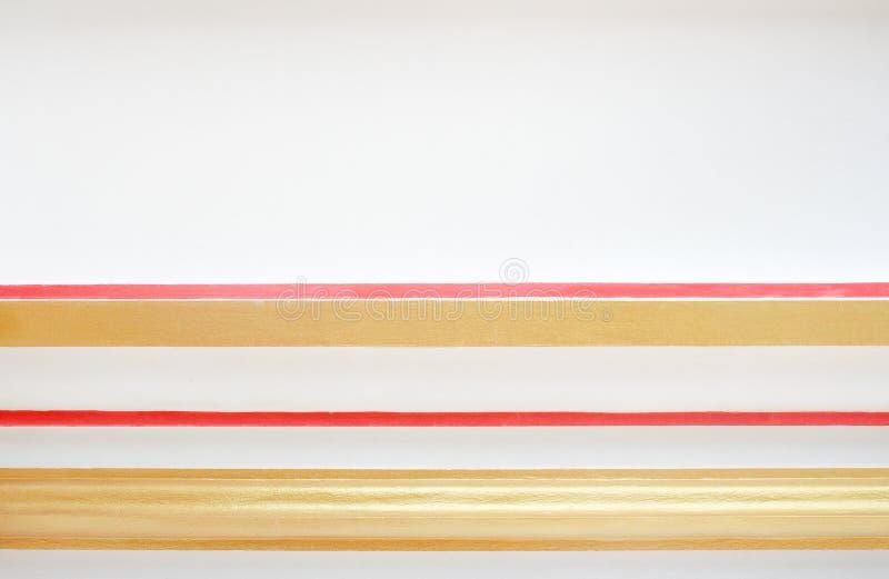 Texturice el oro colorido y la línea roja en extracto horizontal de los modelos en el muro de cemento blanco para el espacio del  imagen de archivo libre de regalías