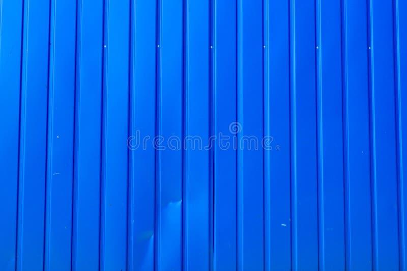 Textuur van de blauwe verticale raad met de naden van het metaalprofiel van het tin De achtergrond stock afbeelding