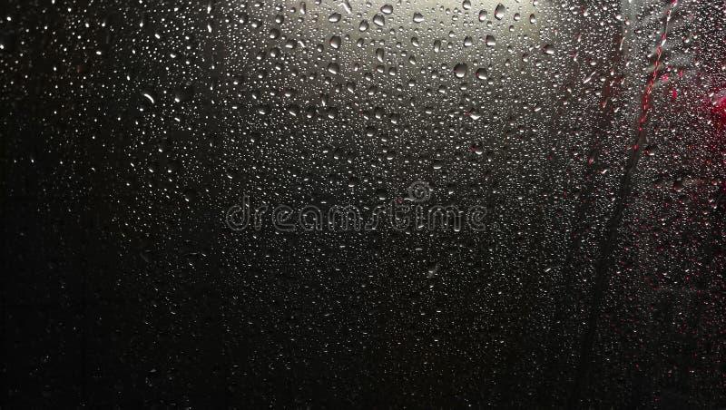 Textuur van de dalingen van regen op het glas stock afbeelding