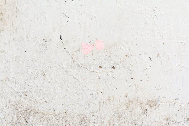 Textuur van de hulp oude witte muur, ongelijke lichtgrijze oppervlakte van het pleister met barsten en deuken stock foto